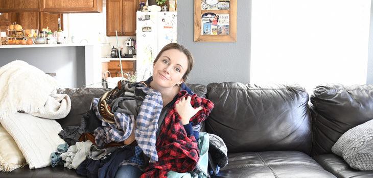 Hannah on sofa holding laundry